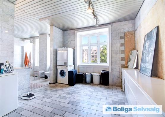 Stort badeværelse med marmorfliser - trænger til istandsættelse.