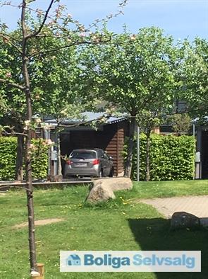 Carport og indgang til huset. Mange grønne arealer i bebyggelsen.