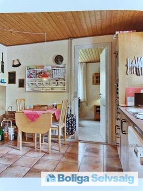 Spiseplads i ældre, men yderst velholdt og rummeligt køkken. Døre til stue og fordelingsgang.