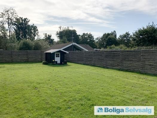 Flot stor sydvendt have, med nyt stort legehus i bjælkehus stilen. Set midt på dagen.