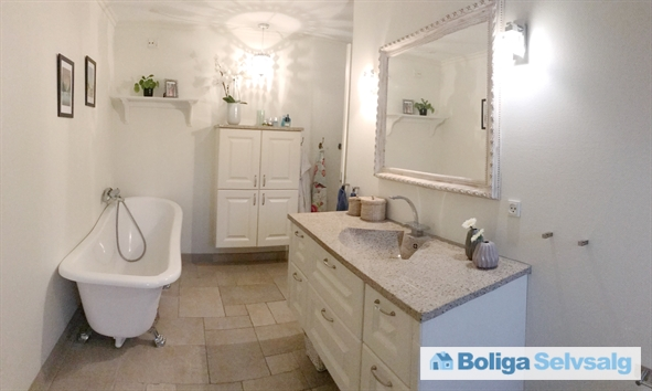 Badeværelse nedenunder med badekar på løvefødder og brusenische.
